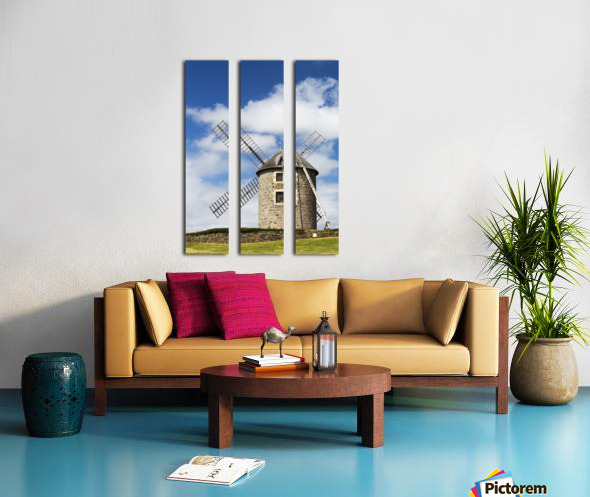 An old stone windmill on a hillside with wooden blades, surrounded by a stone fence with blue sky and clouds; Brehec, Brittany, France Split Canvas print