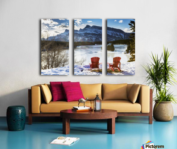 Two red chairs on snow covered ridge overlooking frozen lake with snow covered mountain in the background with blue sky and clouds; Banff, Alberta, Canada Split Canvas print