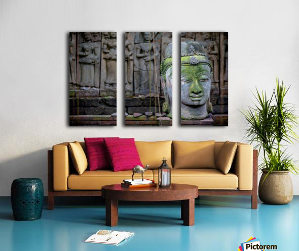 A terra cotta head of buddha sits in front of bas-relief in a terra cotta garden; Chiang Mai, Thailand Split Canvas print
