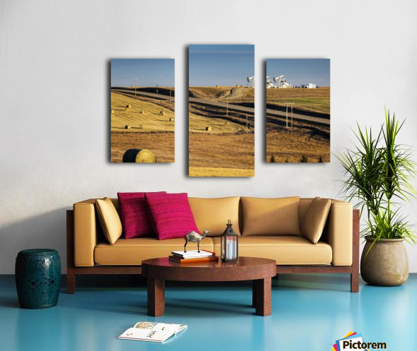 Two pump jacks on rolling hills in the distance along highway with cut fields and hay bales; Alberta, Canada Canvas print