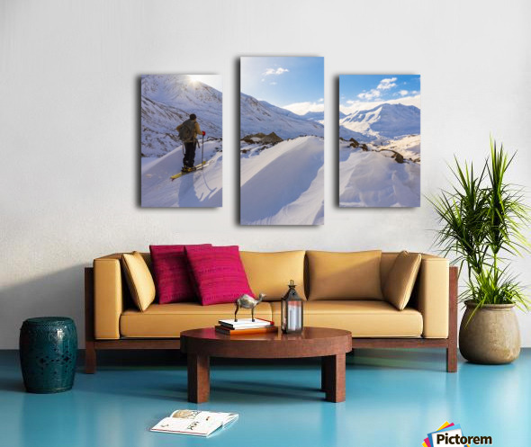A backcountry skier looks over the Black Rapids Glacier valley from a high point on the terminal moraine in winter; Alaska, United States of America Canvas print