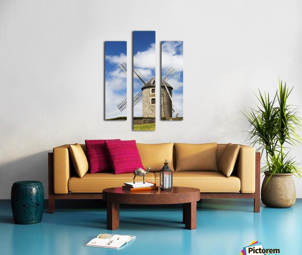An old stone windmill on a hillside with wooden blades, surrounded by a stone fence with blue sky and clouds; Brehec, Brittany, France Canvas print
