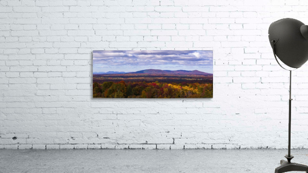 Mountain range in autumn colours with autumn coloured forest in the foreground; West Bolton, Quebec, Canada
