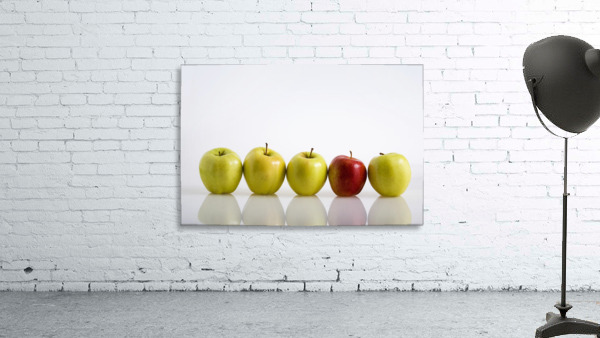 Four Yellow Apples With One Red Apple In A Row On A Reflective Surface; Calgary, Alberta, Canada