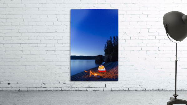 A campfire built on a beach at dusk next to a glowing tent, tranquil ocean water reflecting the warm light, Hesketh Island; Homer, Alaska, United States of America
