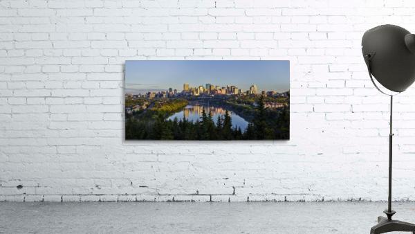 Skyline of downtown Edmonton reflected in the North Saskatchewan River under a blue sky; Edmonton, Alberta, Canada