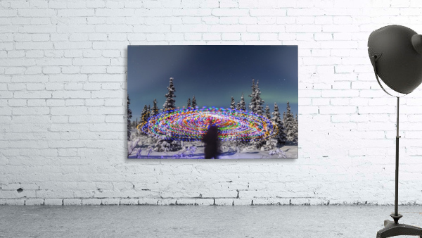 The Aurora Borealis dances over the top of a vibrant spiral light painting, the blurry figure of a man in the middle of the light painting, moonlight casting shadows on snow covered spruce trees on a clear winter night, interior Alaska; Gakona, Alaska, Un