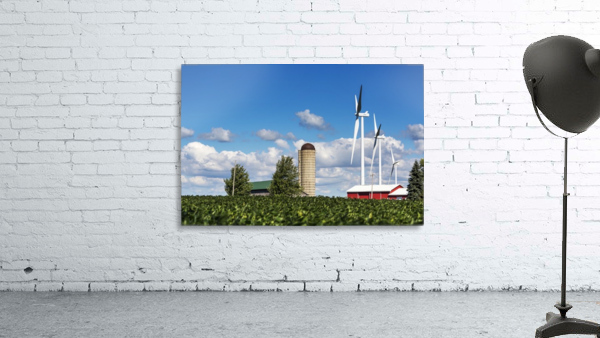 Large metal windmills in a farm yard with red barn and silo, soy bean field in the foreground and blue sky and clouds in the background; Ontario, Canada