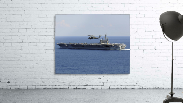 An MH-60S Seahawk helicopter flies over USS George H.W. Bush.