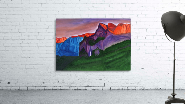 Snowy peaks of the mountains with a waterfall lit up by the orange dawn