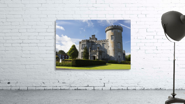 Stone castle with turret, manicured grass, gardens, fountain, blue sky and clouds; County Clare, Ireland