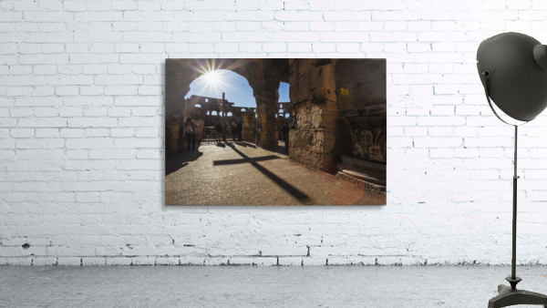 Sunburst through an archway at the Colosseum and a shadow of a cross; Rome, Italy