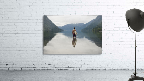 A Young Man Wearing A Swimsuit Stands In Cameron Lake; British Columbia Canada