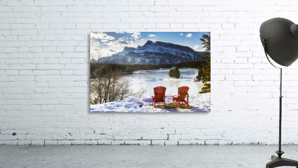 Two red chairs on snow covered ridge overlooking frozen lake with snow covered mountain in the background with blue sky and clouds; Banff, Alberta, Canada