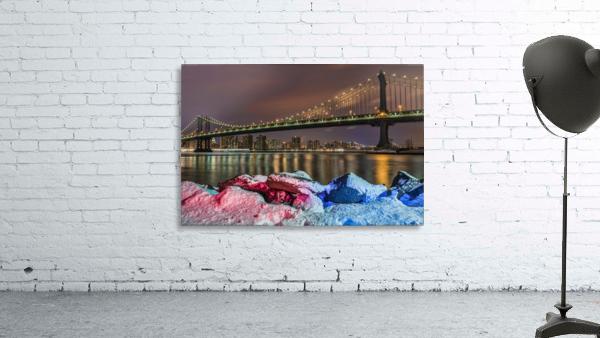 Manhattan Bridge by snow-covered rocks at sunset, Brooklyn Bridge Park; Brooklyn, New York, United States of America