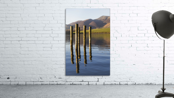 Wooden posts reflected in tranquil after with mountains the the background; Keswick, Cumbria, England