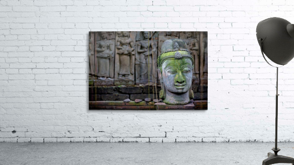 A terra cotta head of buddha sits in front of bas-relief in a terra cotta garden; Chiang Mai, Thailand