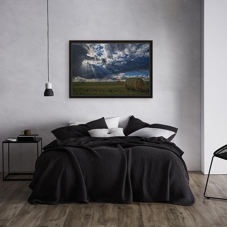 Sunlight breaks through the storm clouds over a field of hay bales; Saskatchewan, Canada  Art