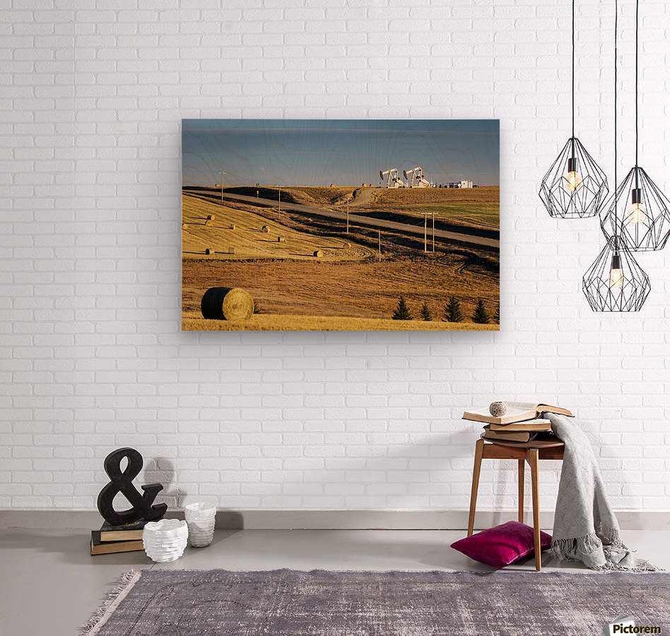 Two pump jacks on rolling hills in the distance along highway with cut fields and hay bales; Alberta, Canada  Wood print