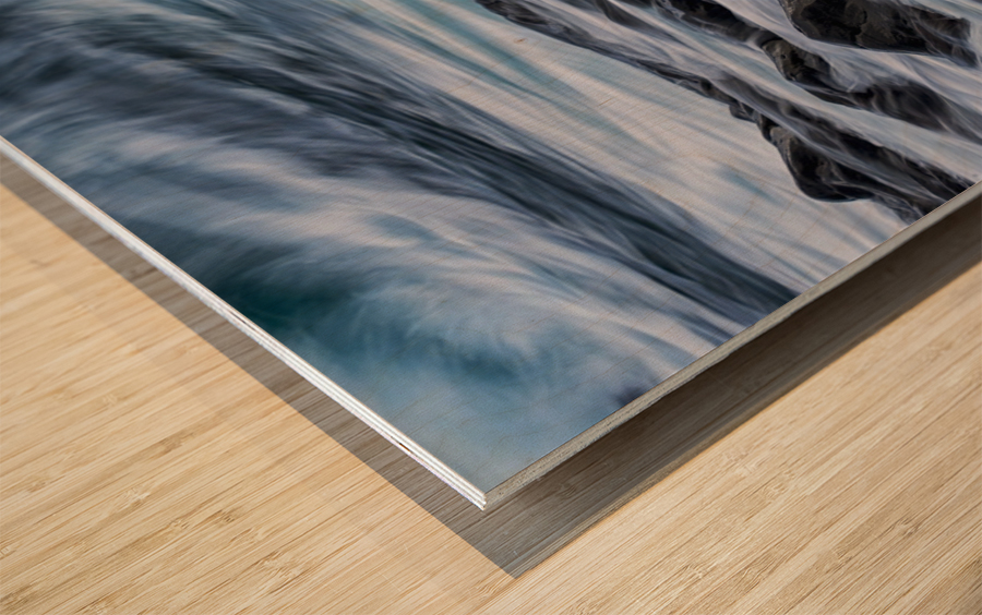Long exposure of waves striking the coastline and flowing over rocks; Iceland Wood print