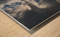 Sunlight breaks through the storm clouds over a field of hay bales; Saskatchewan, Canada Wood print