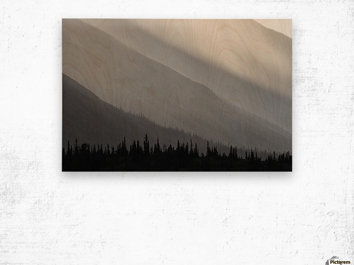Light shines through the rain as it falls on the mountains along the Wind River in the Peel Watershed; Yukon, Canada Wood print