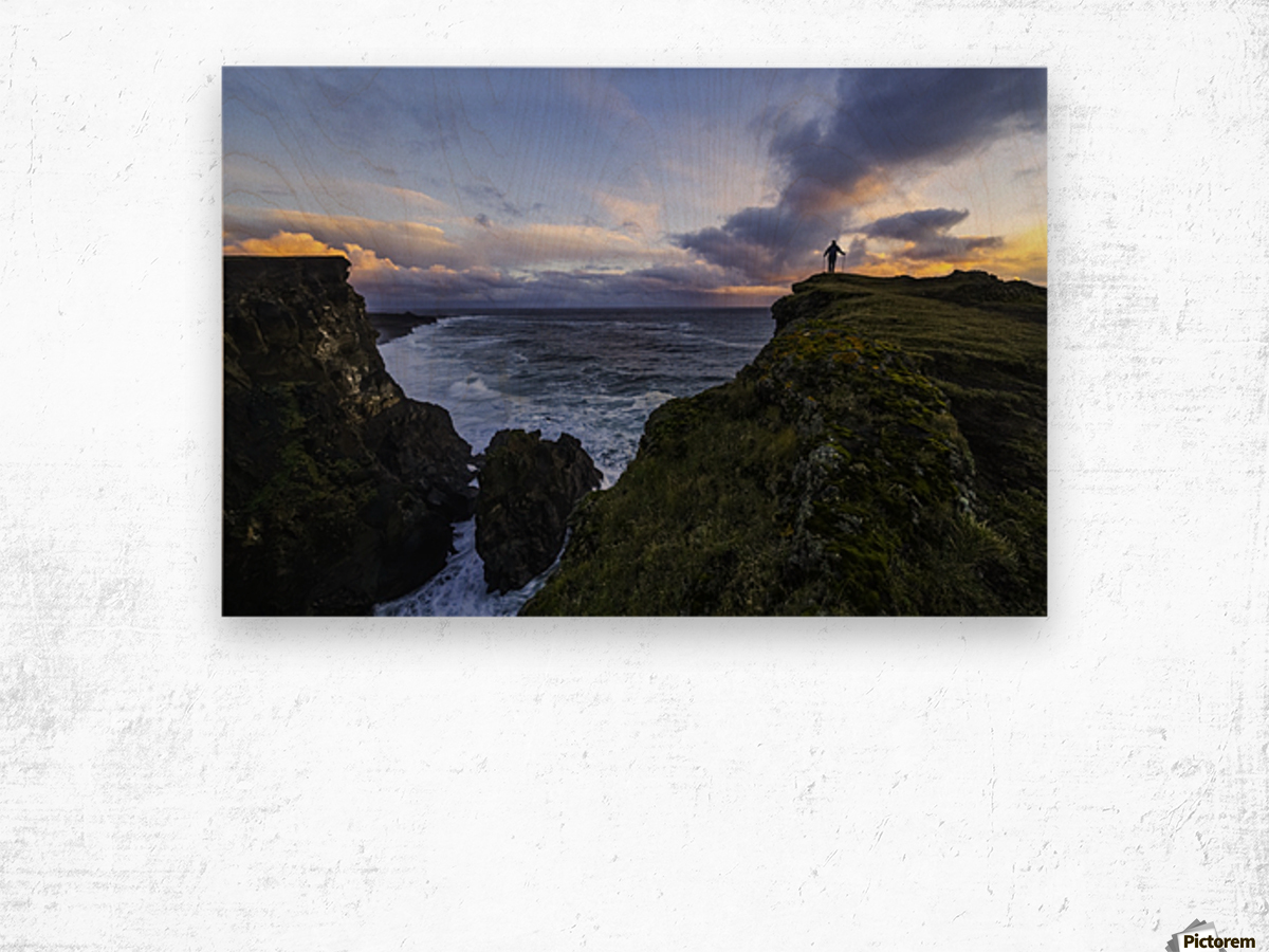 Person standing on a cliff face while the Atlantic Ocean pounds the shores beneath them; Iceland Wood print