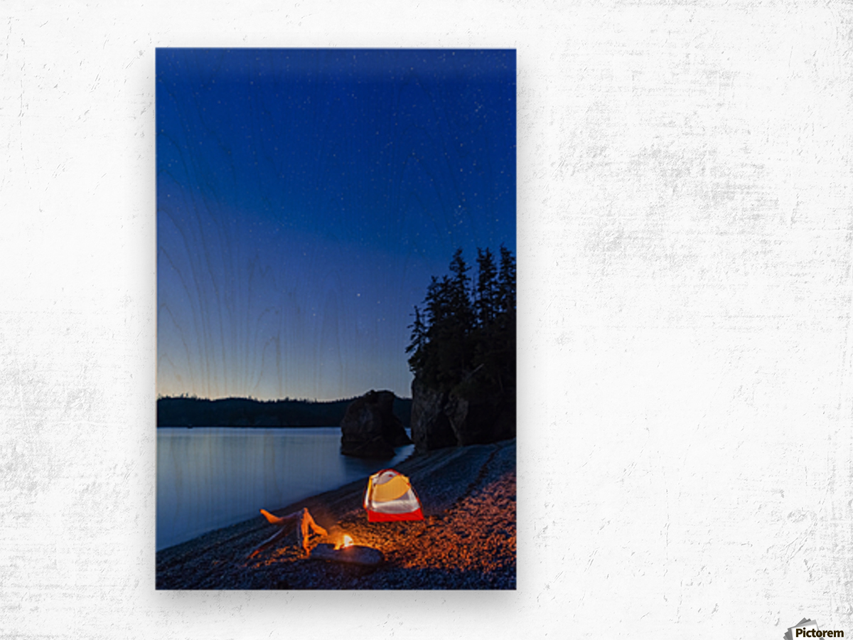 A campfire built on a beach at dusk next to a glowing tent, tranquil ocean water reflecting the warm light, Hesketh Island; Homer, Alaska, United States of America  Wood print