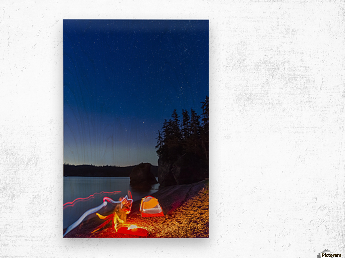 A campfire built on a beach at dusk next to a glowing tent and headlamp light trails, tranquil ocean water reflecting the warm light, Hesketh Island; Homer, Alaska, United States of America  Wood print