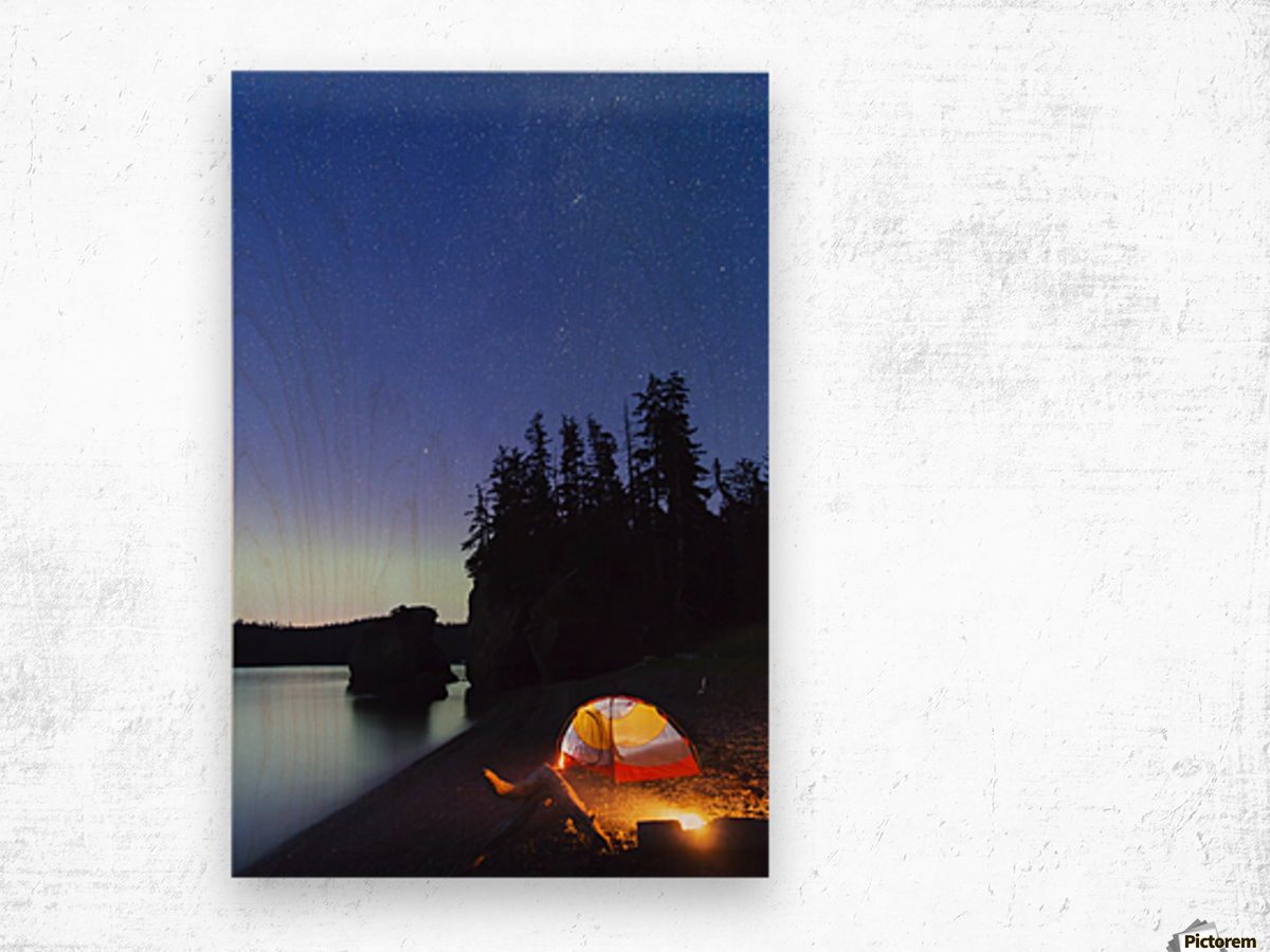 A glowing tent on a beach overlooks green Aurora Borealis reflected in the tranquil ocean water, Hesketh Island; Homer, Alaska, United States of America  Wood print
