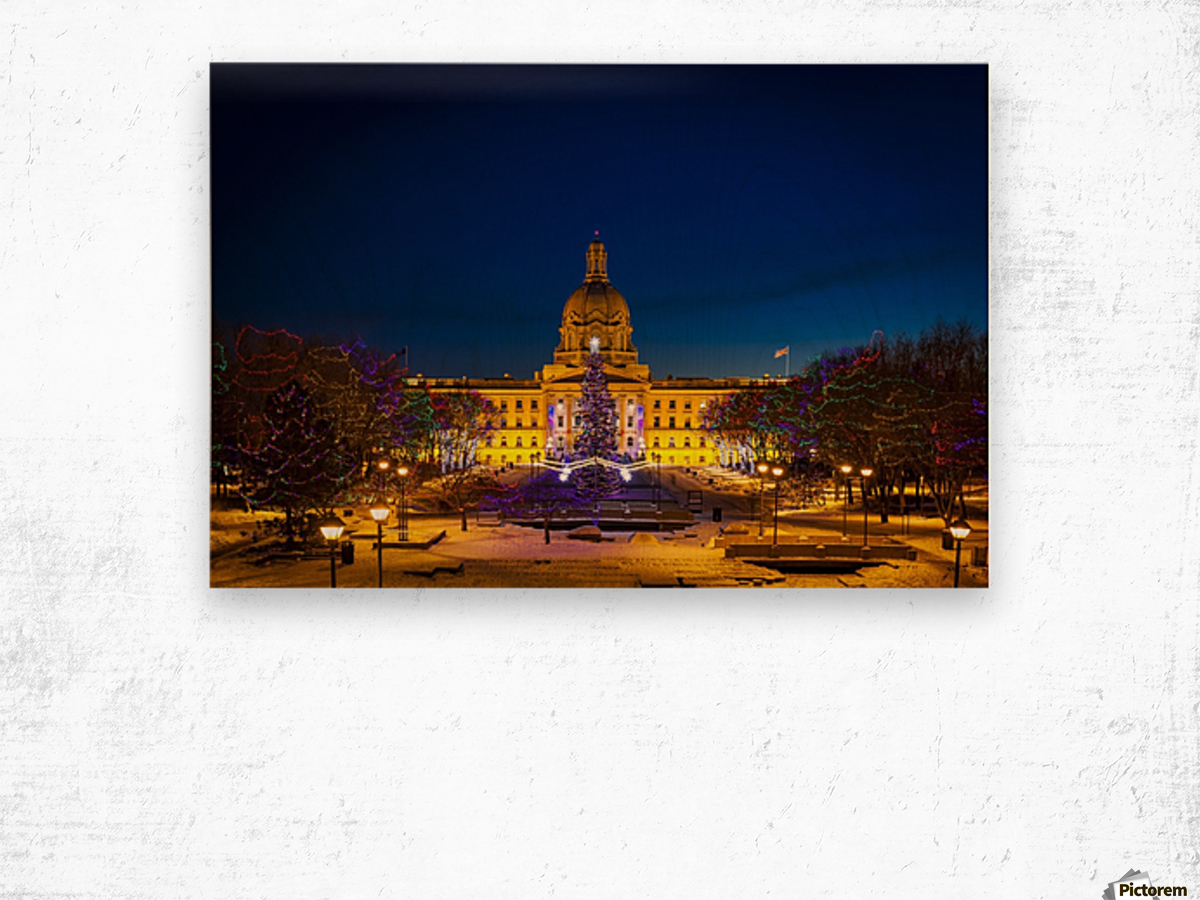 Alberta Legislature building illuminated and a Christmas tree with colourful lights on the trees for decoration at Christmas time; Edmonton, Alberta, Canada Wood print