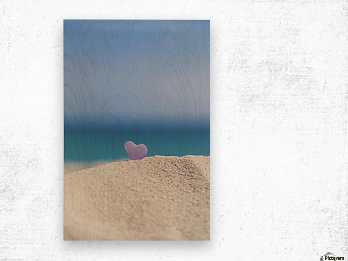 A lavender heart shaped sea glass in the sand at the beach; Honolulu, Oahu, Hawaii, United States of America Wood print