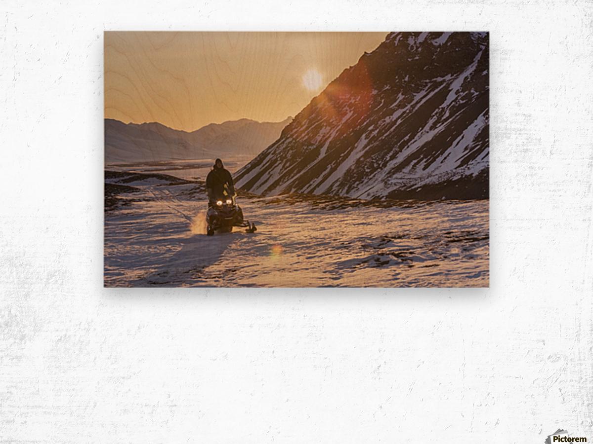Man riding a snowmachine up the Anaktuvuk River Valley at sunset, Gates of the Arctic National Park, Brooks Range, Arctic Alaska Wood print