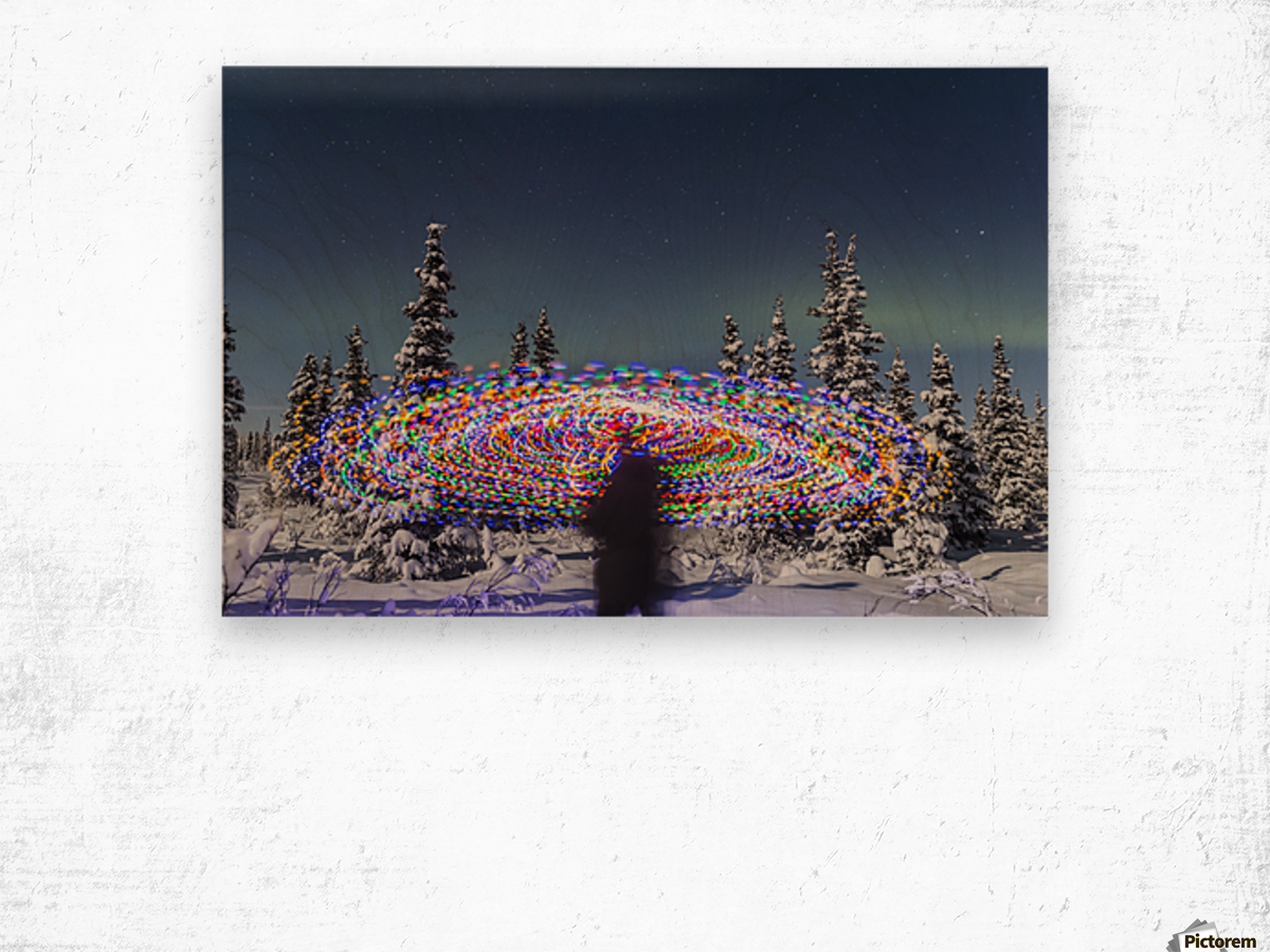 The Aurora Borealis dances over the top of a vibrant spiral light painting, the blurry figure of a man in the middle of the light painting, moonlight casting shadows on snow covered spruce trees on a clear winter night, interior Alaska; Gakona, Alaska, Un Wood print