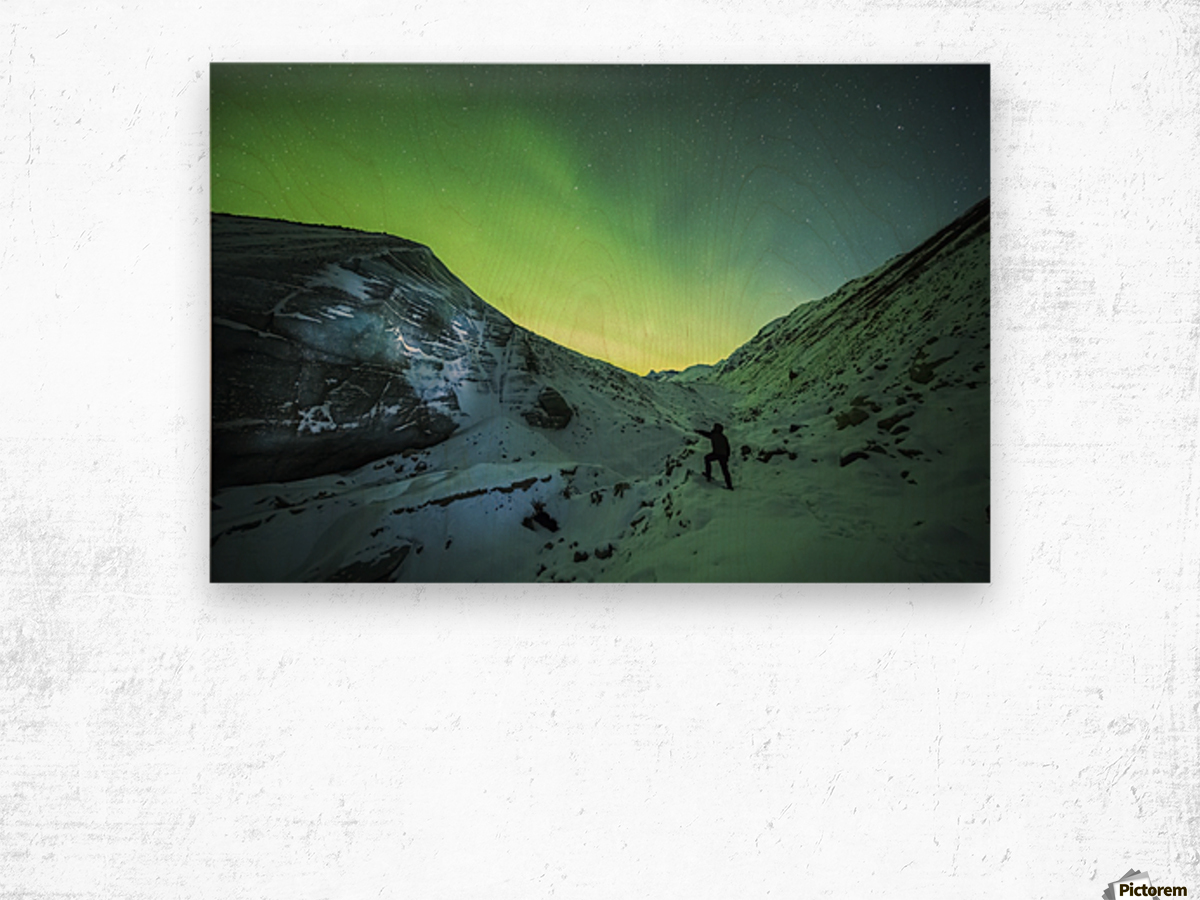 A man lights up the ice of Castner Glacier with a flashlight underneath a diffuse aurora display; Alaska, United States of America Wood print