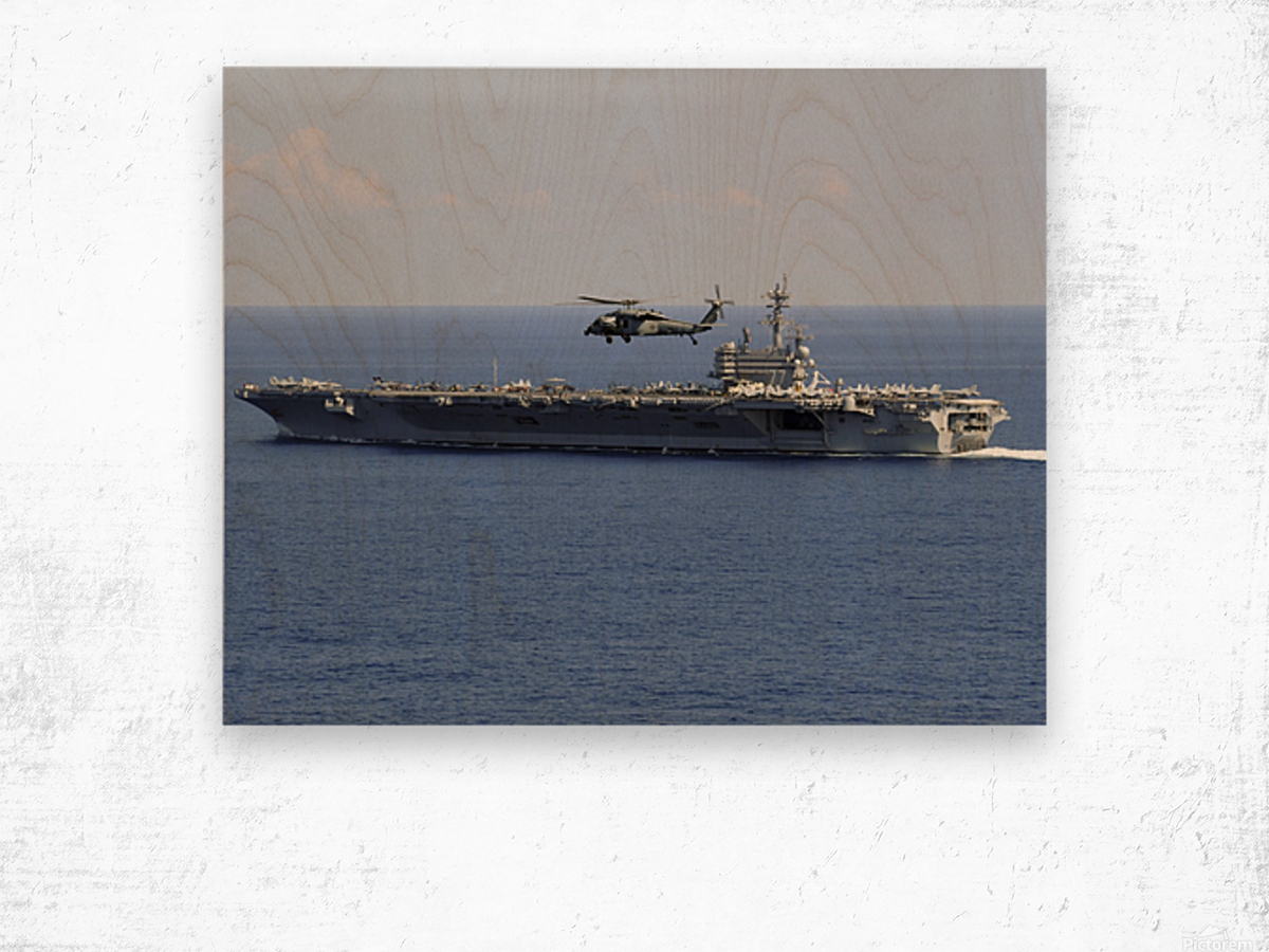 An MH-60S Seahawk helicopter flies over USS George H.W. Bush. Wood print