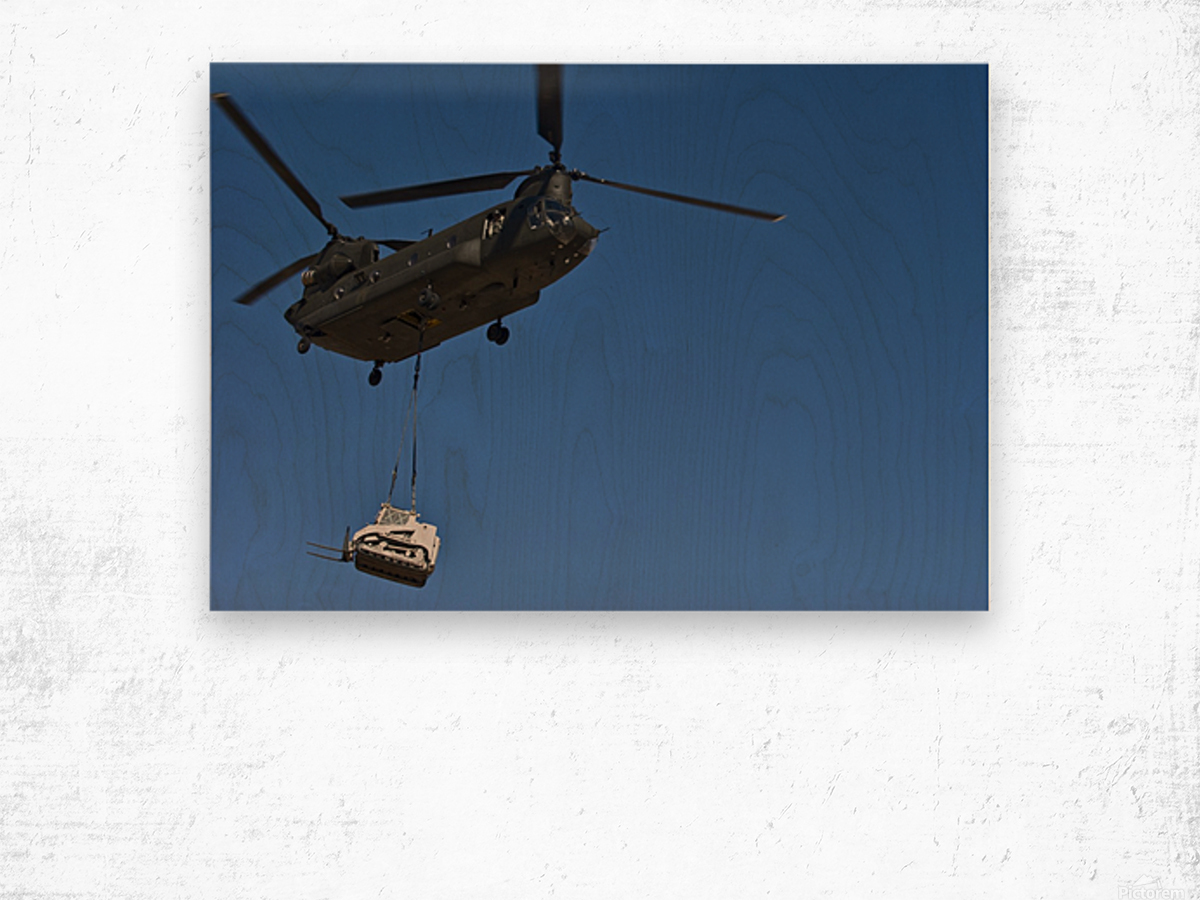 A U.S. Army CH-47 Chinook carries a bulldozer to a drop site. Wood print