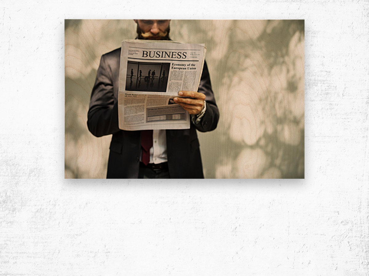 A bearded man reading the business section of a newspaper Wood print