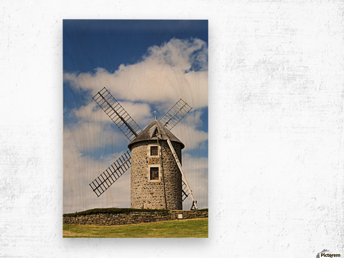 An old stone windmill on a hillside with wooden blades, surrounded by a stone fence with blue sky and clouds; Brehec, Brittany, France Wood print