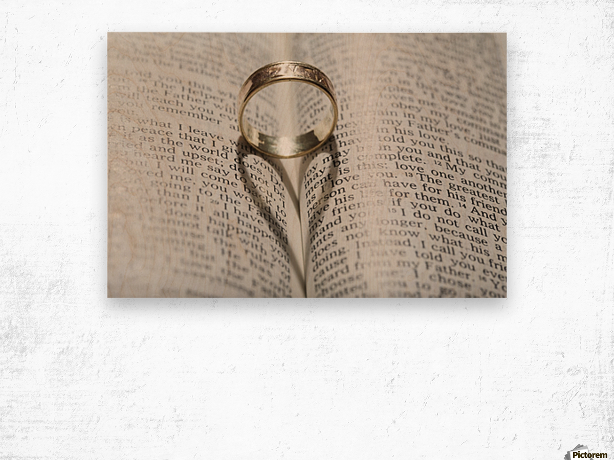Close up of a gold ring with the shadow of an heart on book about love;Calgary Alberta Canada Wood print