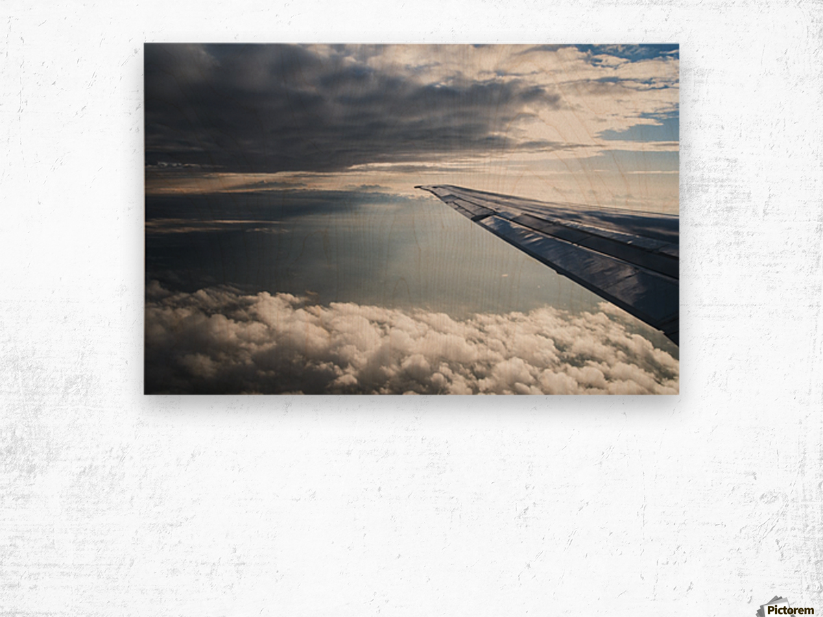 A commercial jet flies through the clouds; Colorado, United States of America Wood print