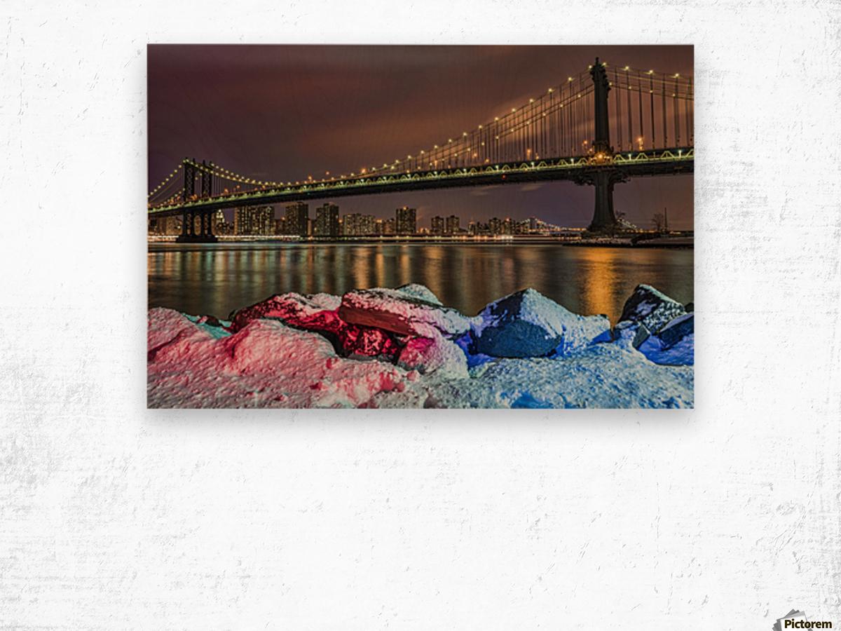 Manhattan Bridge by snow-covered rocks at sunset, Brooklyn Bridge Park; Brooklyn, New York, United States of America Wood print