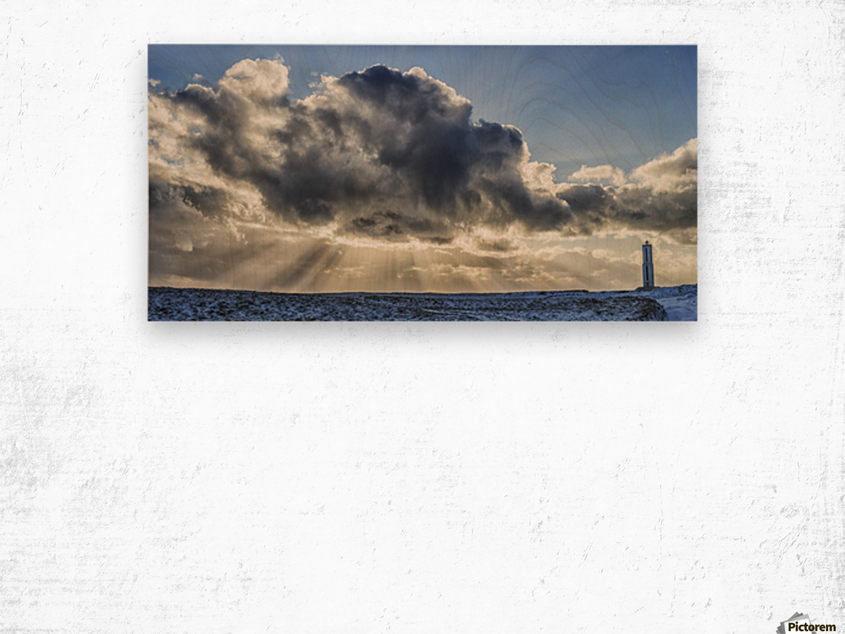 Rays of light shine out from behind the clouds in the skies above a lightnouse along the southern shore of Iceland; Iceland Wood print