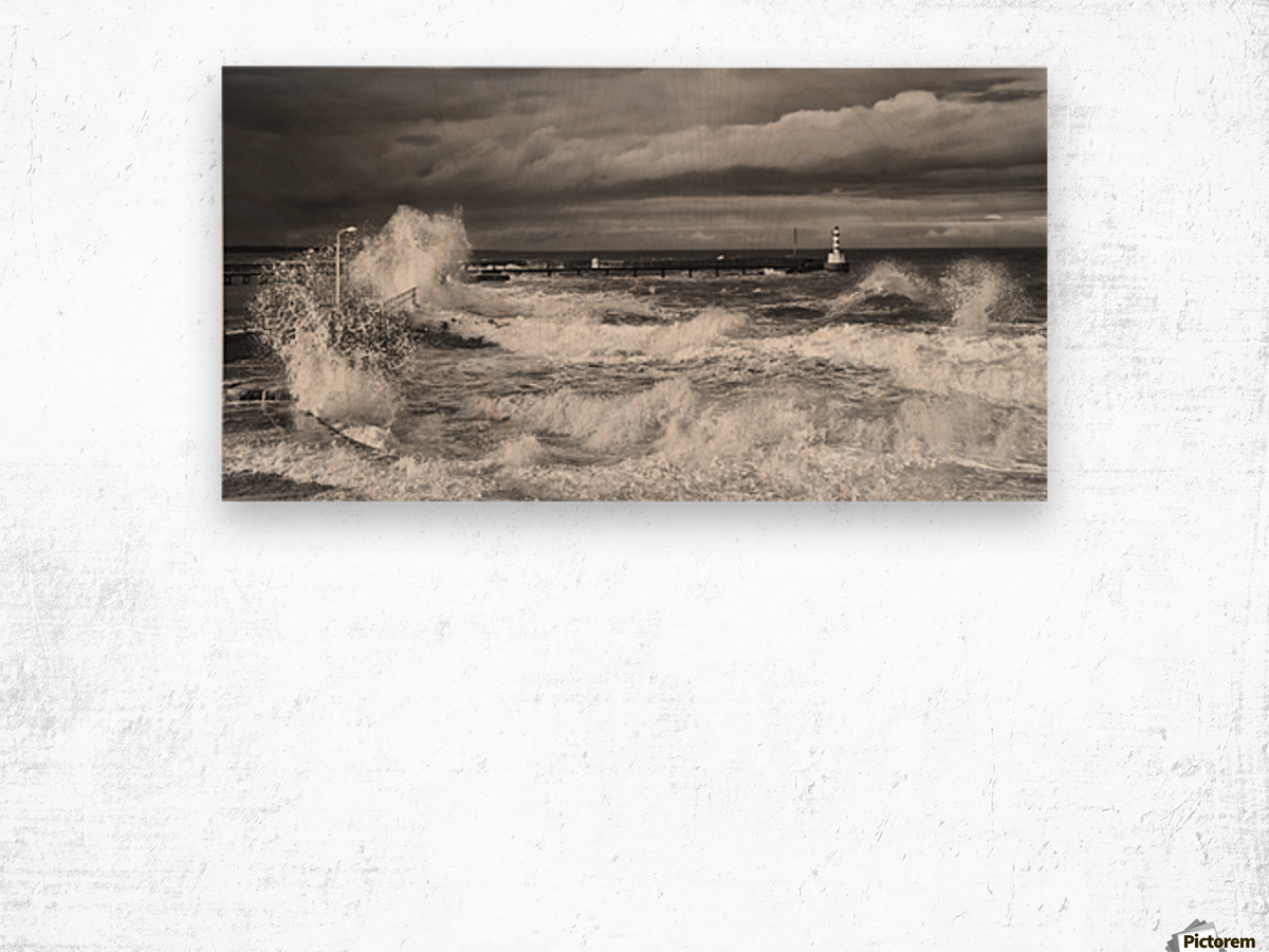 Waves crashing along the coast with a small lighthouse at the end of a pier; Amble, Northumberland, England Wood print