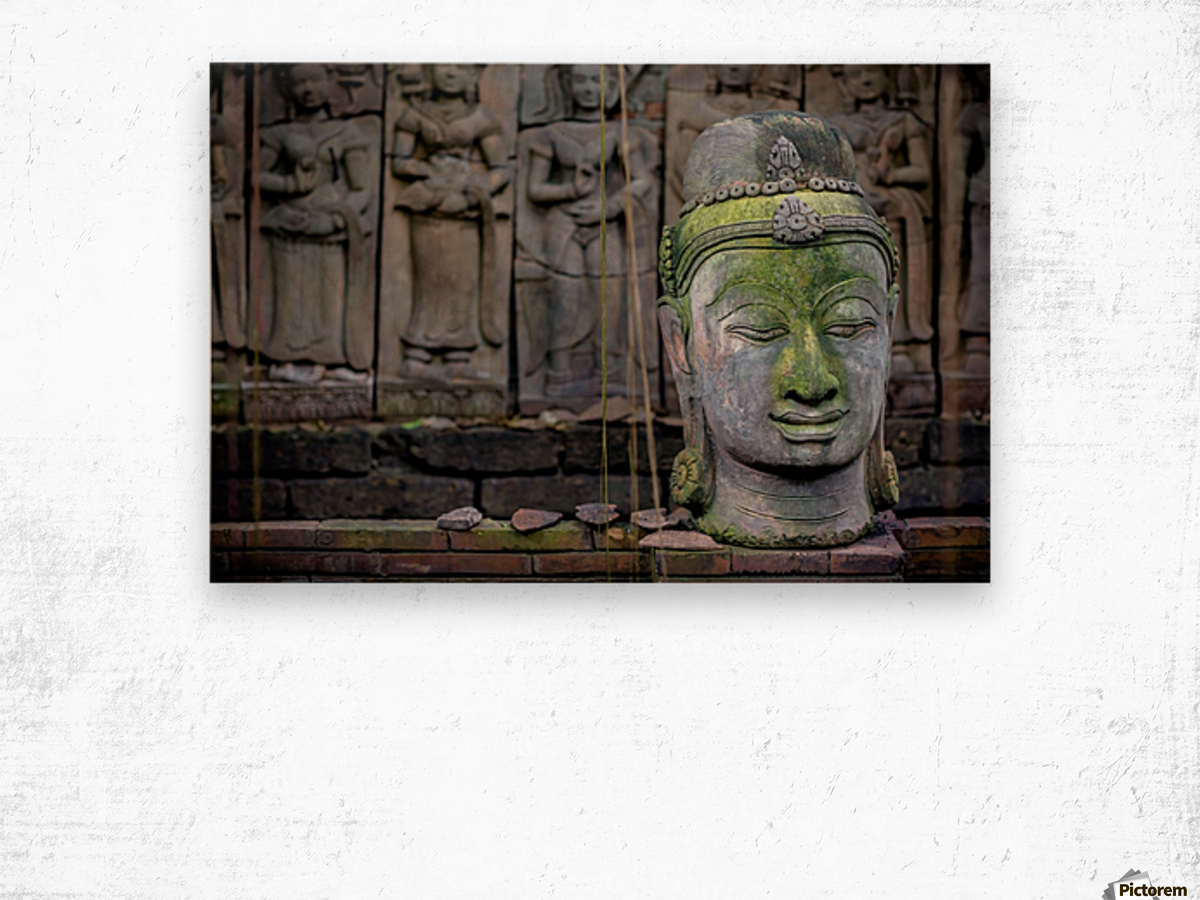 A terra cotta head of buddha sits in front of bas-relief in a terra cotta garden; Chiang Mai, Thailand Wood print