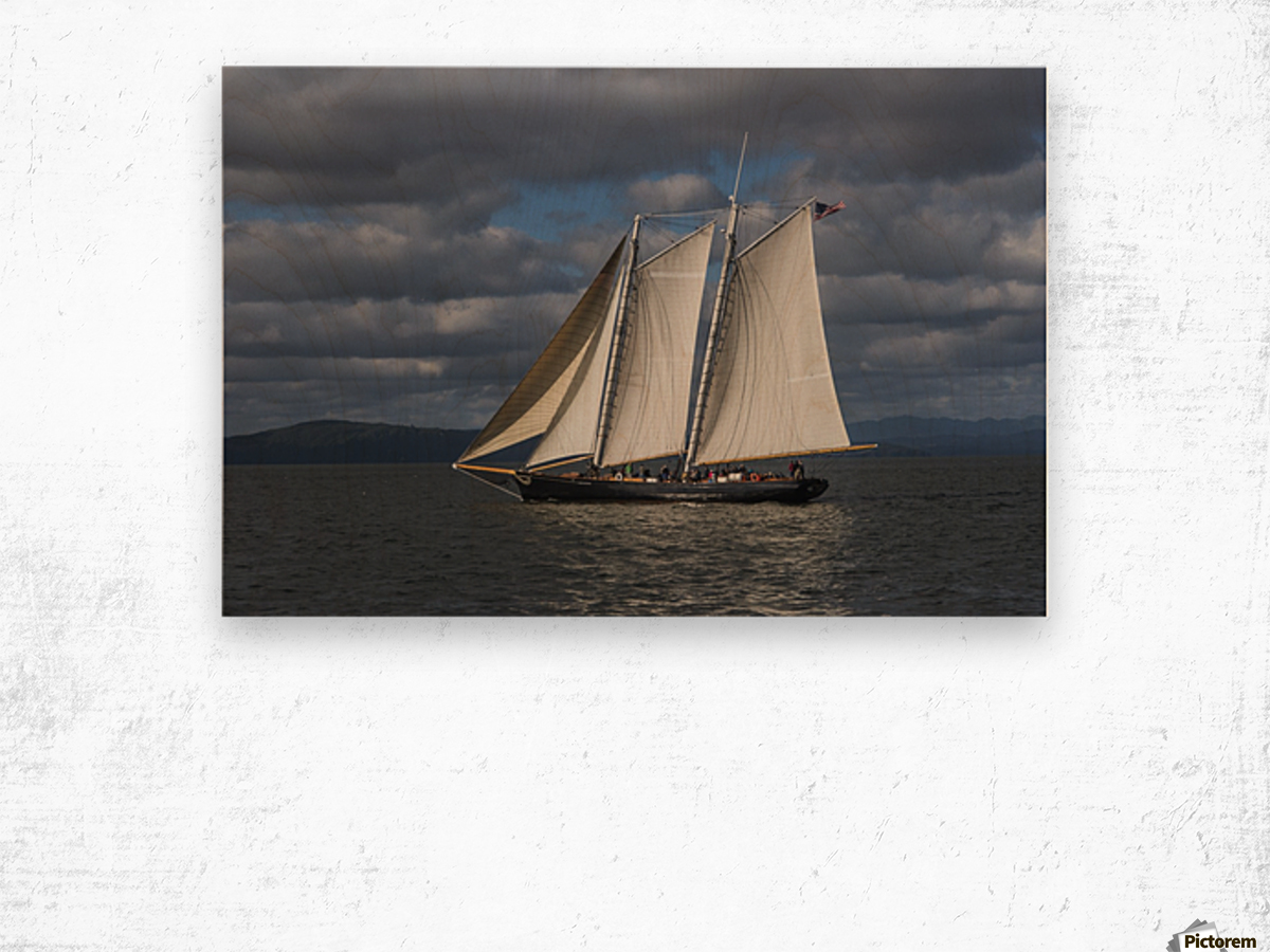 A large sailboat sails down the Columbia River; Astoria, Oregon, United States of America Wood print